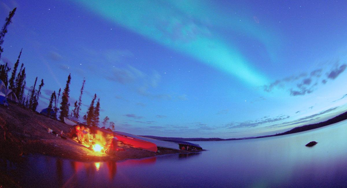 Photo by Tessa Macintosh - Fire on lake under Northern Lights
